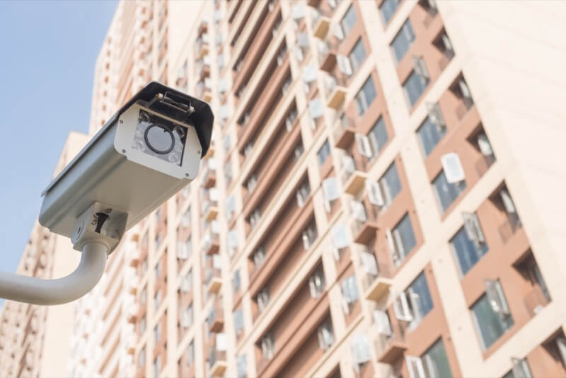Picture of a surveillance camera with an apartment building in the background