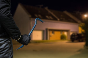 Picture of a burglar with a crowbar stalking a house