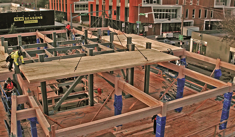 Structural loads are borne by a grid of glulam posts tied to the deep piles onto which CLT panels are lifted and locked into place over steel tubes welded onto heavy steel plates attached to the ends of the columns. (Kaiser Group)