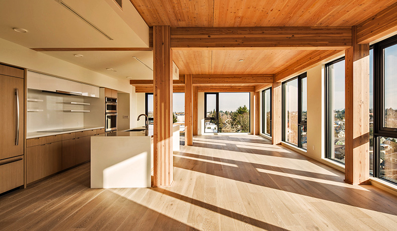 Above: The combination of exposed CLT wooden ceilings and exposed glulam posts and beams on a grid with oak floors lends a warm wooden patina to the units, offset by vertical white drywall panels between the windows on the three sides of the unit and in the kitchens and bathrooms. Below: Each unit has a 16.5-by-11.3-foot (5 by 3.5 m) deck facing north or south. (Andrew Pogue)