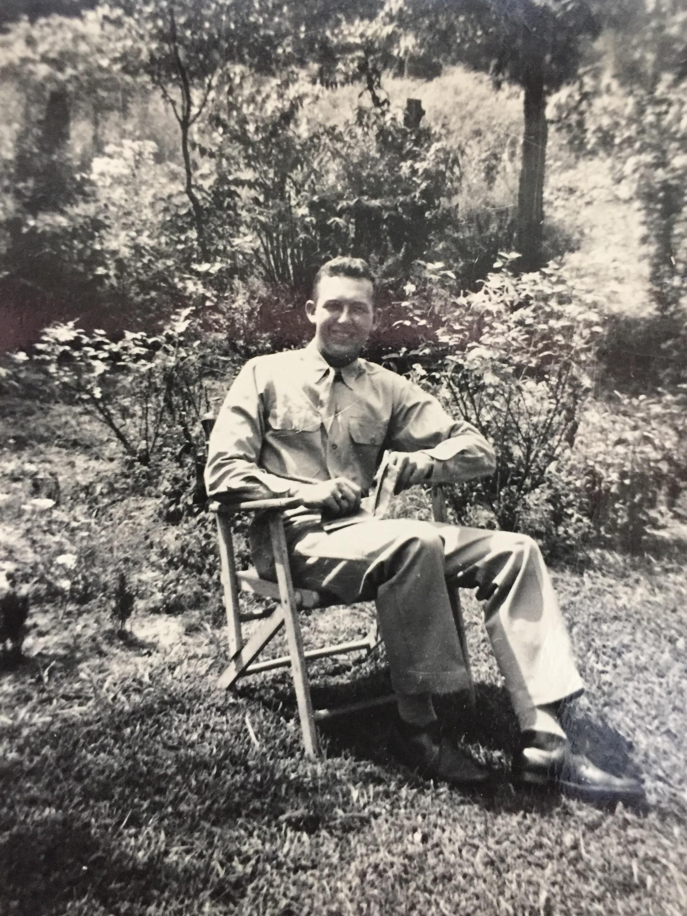 Gene hatfield in war uniform sitting in chair in yard 1944.jpg