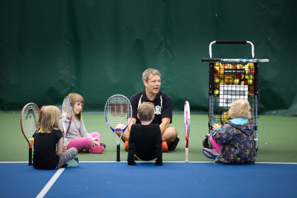 TJ with young kids on sitting court.jpg