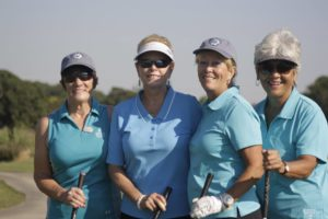 A team of four women dressed in blue polo shirts, holding golf clubs