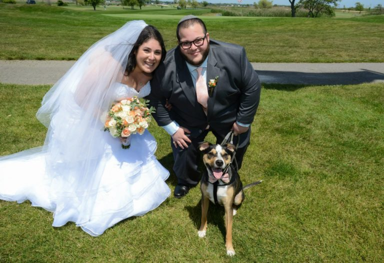 Casey and Samson on their wedding day posing with Jackson