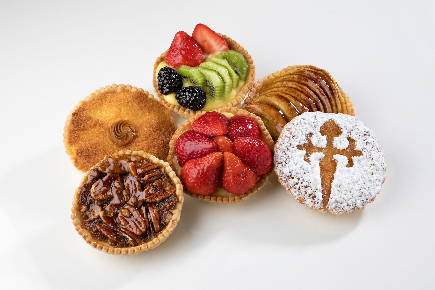 Strawberry, pecan, apple, and traditional tartaletas displayed on a table.