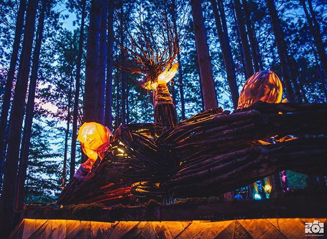 My favorite dusk shot of this year's main sculptural addition, a tiered fountain with gentle giant reclining beings gazing outward through the forest. I loved watching water trickle through the root centerpiece, which was an unplanned part of the fountain 🌲👽🌲 ... .. . Jardín de Sueños created by @tigrebailando for @electric_forest ✨ . .. ... . . . . . #electricforest #ef #festival #art #ef2019 #installationart #sculpture #tigrebailando #carpentry #artlife #forest #exploremore #makersmovement #artofvisuals #visualsoflife #summer #getoutside #explore #fountain #arty #artphotography #lifestyle #festivalphotography #nikon #nikonusa #createcommune #create #thecreatorclass #exploretocreate