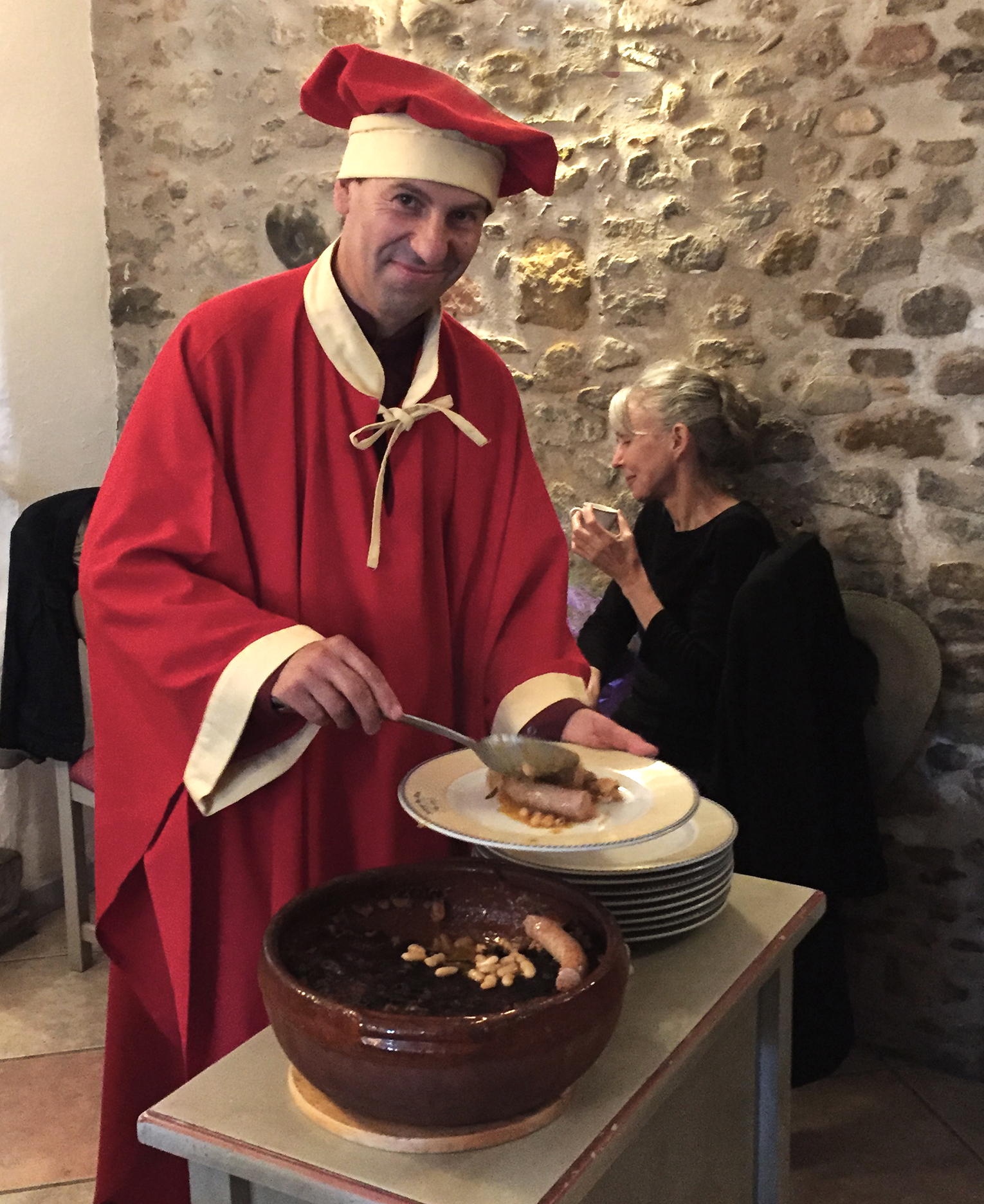 In full confrérie attire to serve cassoulet