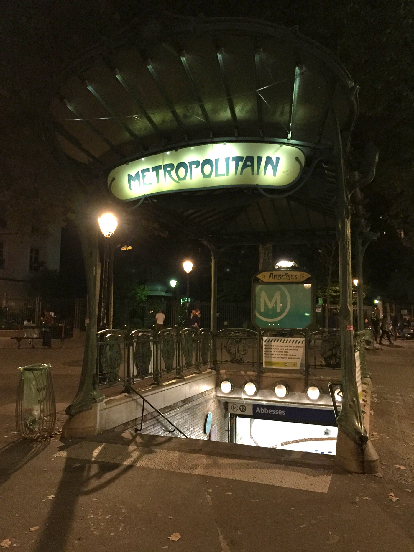 """The only original """"édicule"""" entrance stands at Porte Dauphine but Abbesses also features the distinctive glass roof of the end-of-the-line stations as designed by Guimard. The most common stations (over 100 of them) have molded iron railway surrounding three sides of the stairways, without a roof, as shown on the Cité station at the top of this post."""