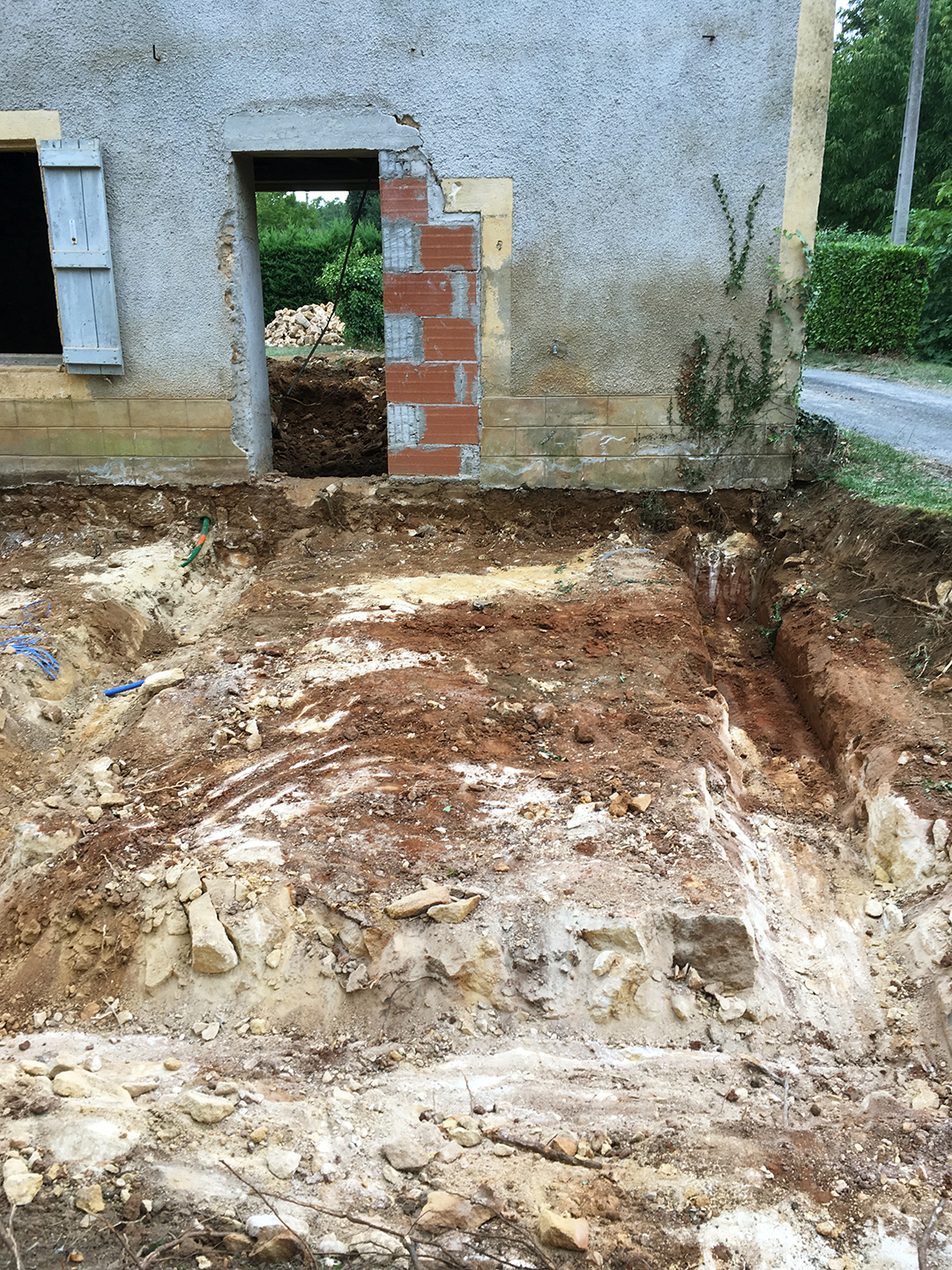 After removing the stone wall on the road side, the masons dug out in front of the old cellar to create the footprint for my future kitchen.