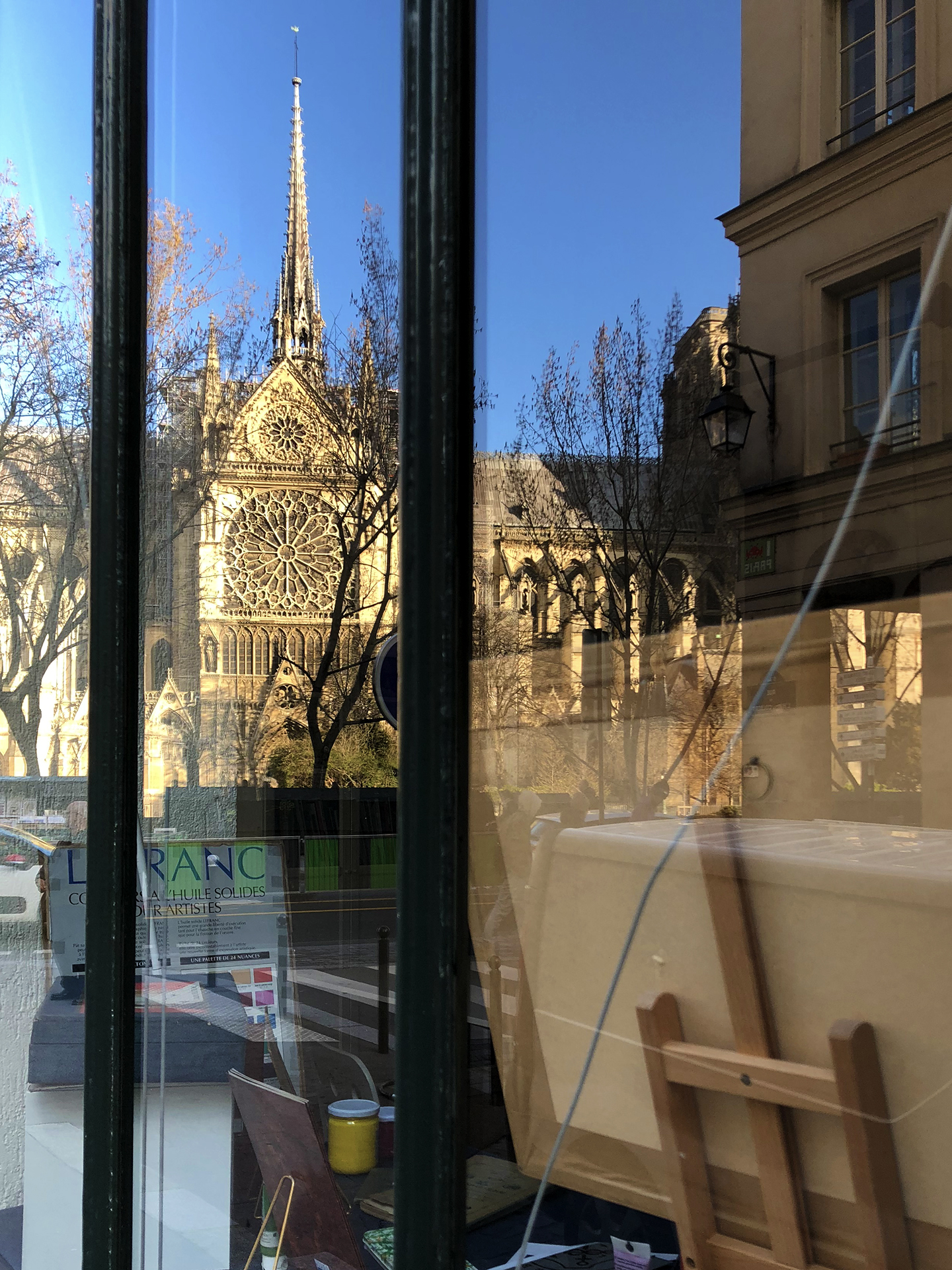 My very last photo of the cathedral. Taken on March 19, 2019. The spire and the South rose reflected in the window of Charbonnel, a fine art supply shop on quai de Montebello.