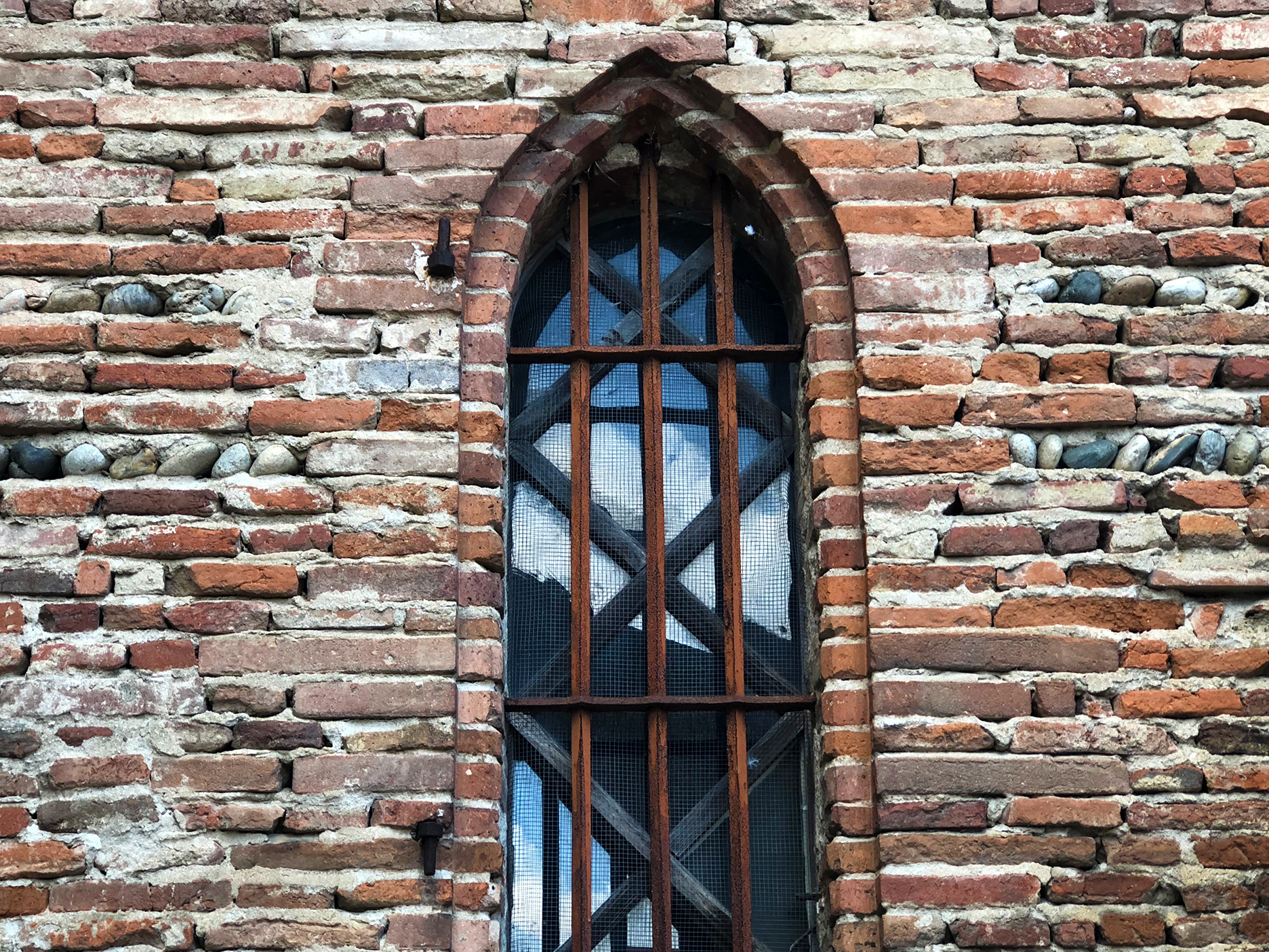 Mostly bricks, a few river stones… Window at the Grenade church.