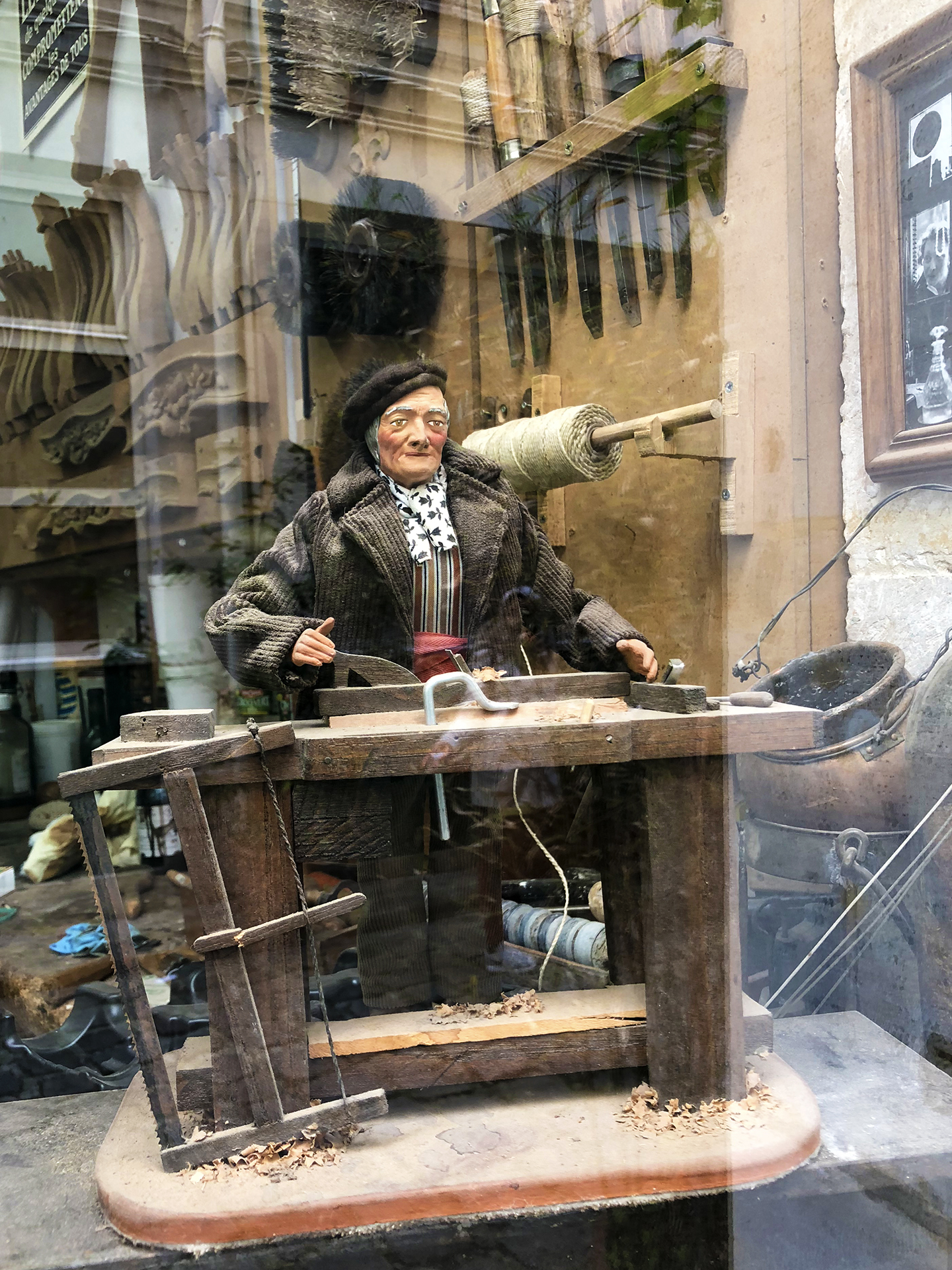 Ebénisterie Straure in cour de l'Ours. The santon of a woodworker sits in the window of the atelier.