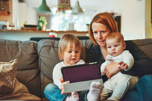 Young mother plays with two small children and iPod while sitting in living room at home