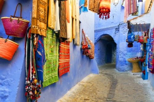 Medina of Chefchaouen Morocco Africa with baskets bright woven fabrics and blue walls.jpg