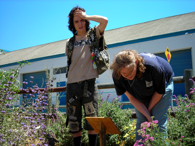 Daniel and Kyra reading new educational signage (purple Bee's Bliss in background, volunteer yellow evening primrose, and pink yarrow).