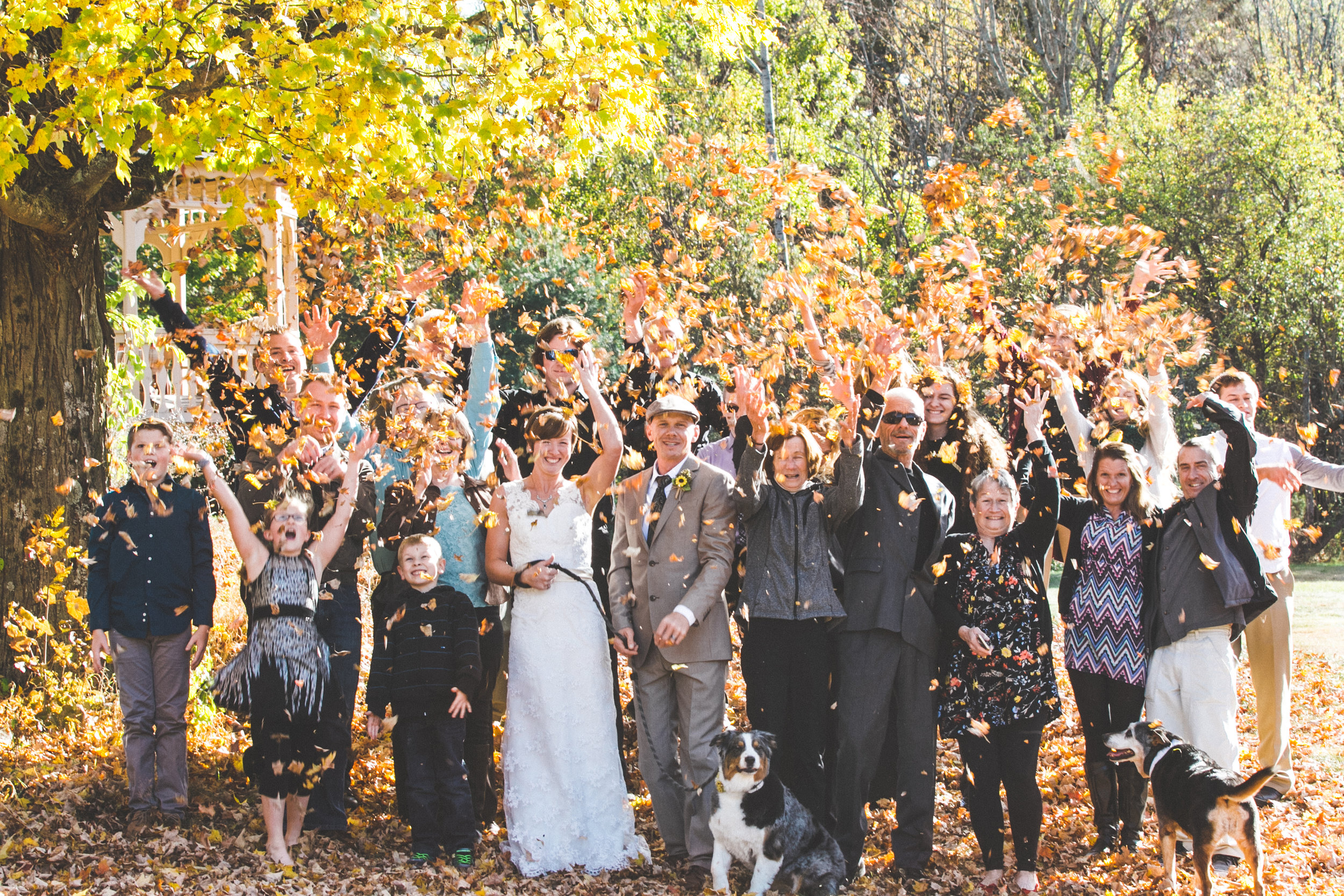 In this fun photo, Elissa and Scott are with their family and friends throwing leaves up into the air for a celebratory feel.