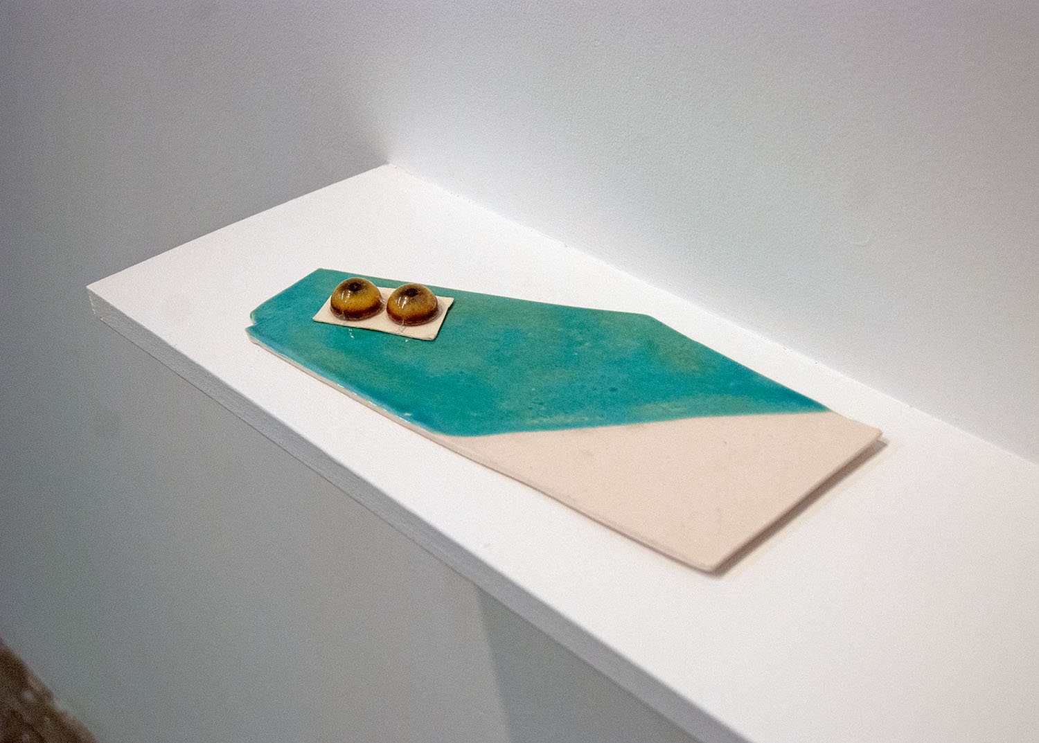 A place where you buy things for sculpture that has glass eyes,  2014, glazed porcelain and glass eyes, .75 x 11 x 5.25 inches