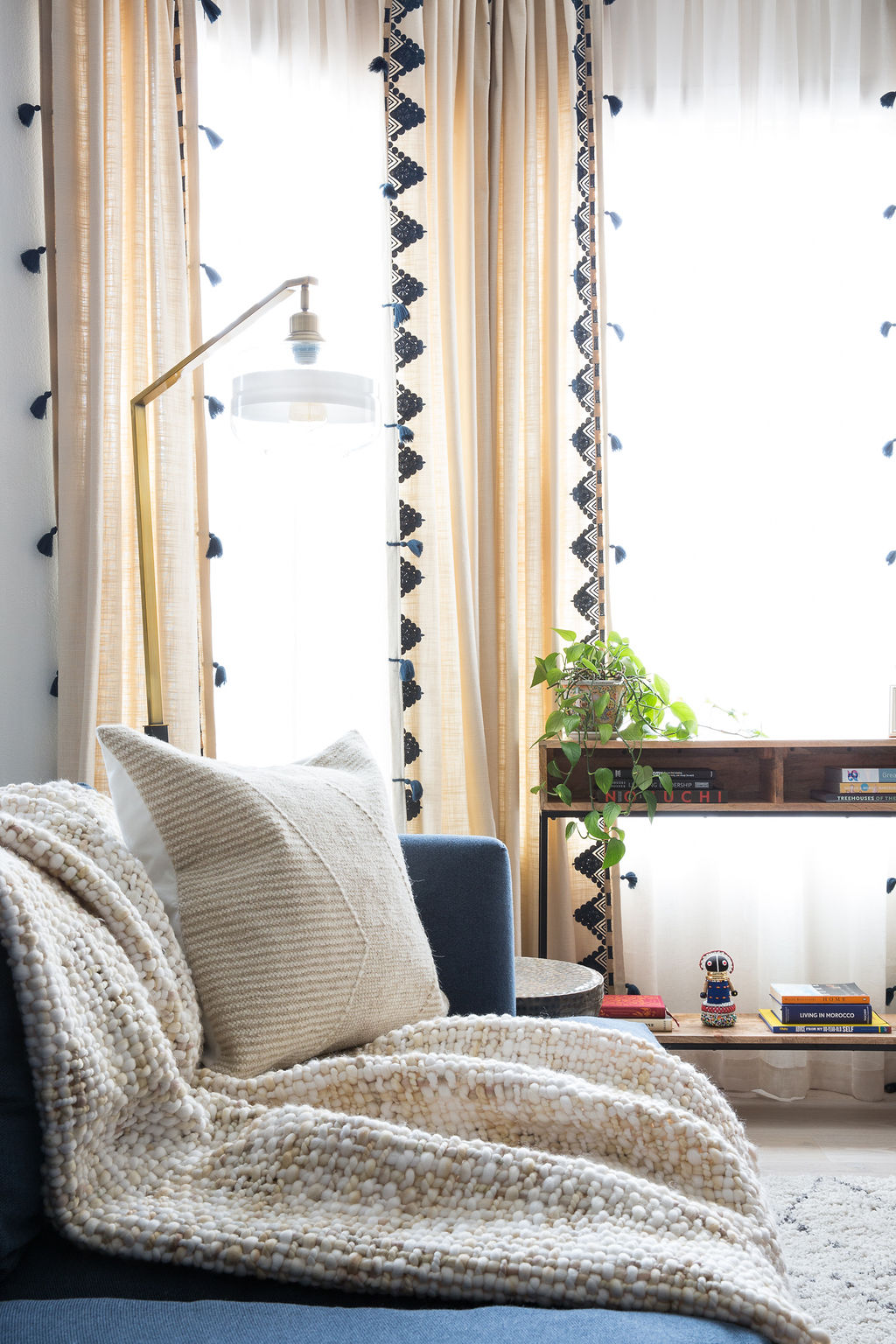Love & Interiors_Cozy_ San Francisco_Living Room_Blue Sofa_Leather Poufs_Tasseled Curtains_Plants.jpg