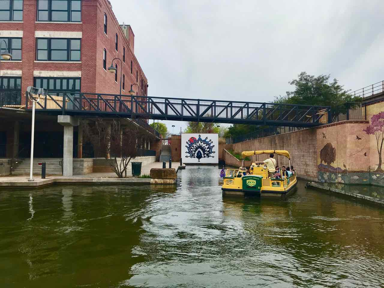 Visitors on the Bricktown Water Taxi enjoy a ride on the west end of the canal. The mural that they are admiring is by Oklahoma artist, Jack Fowler, and is entitled  El Pavo Real  (sometimes referred to as the Bricktown peacock).