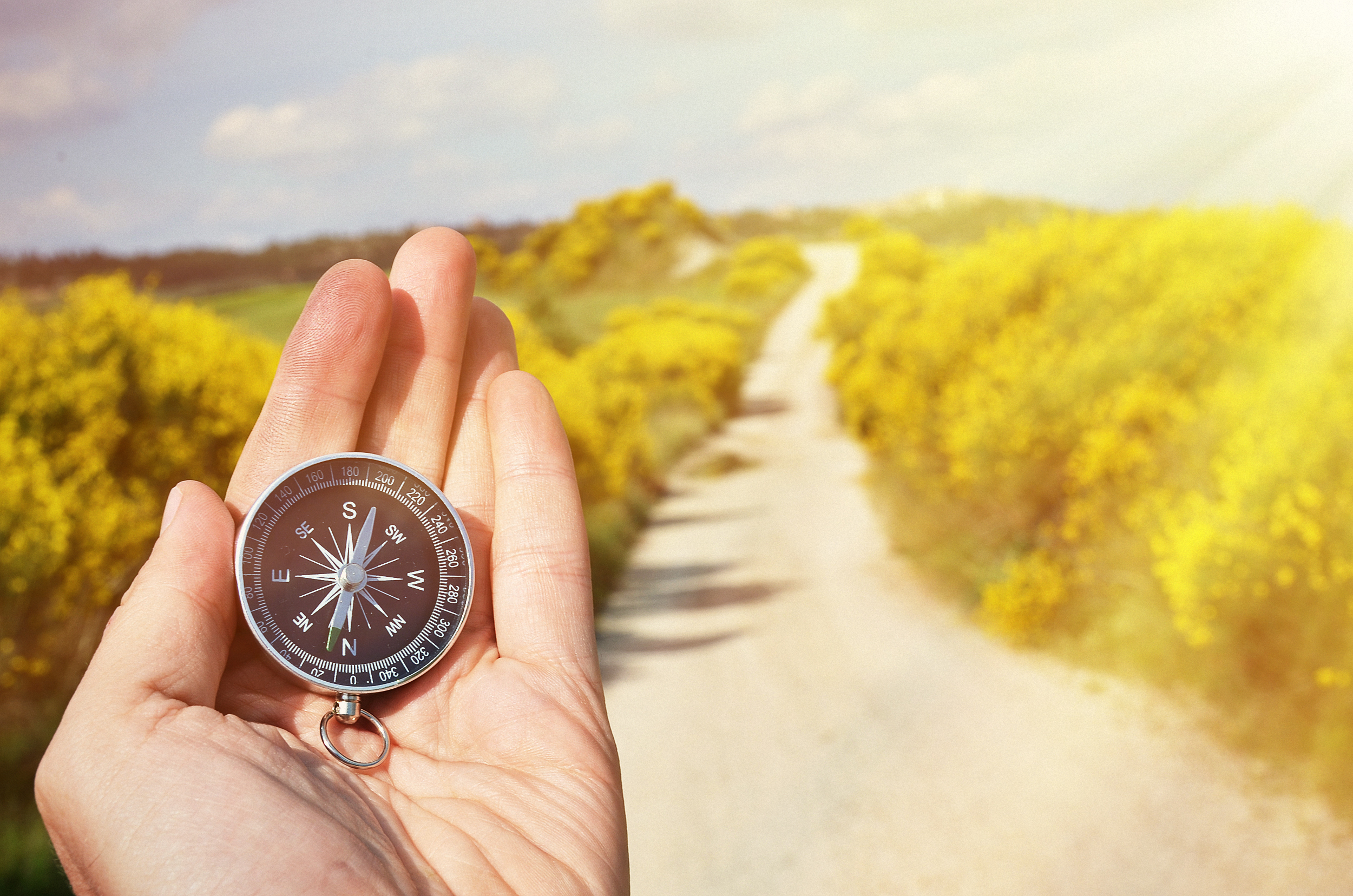 stock-photo-man-holding-a-compass-on-a-fork-in-the-road-on-a-decision-dilemma-direction-concept-472461472.jpg