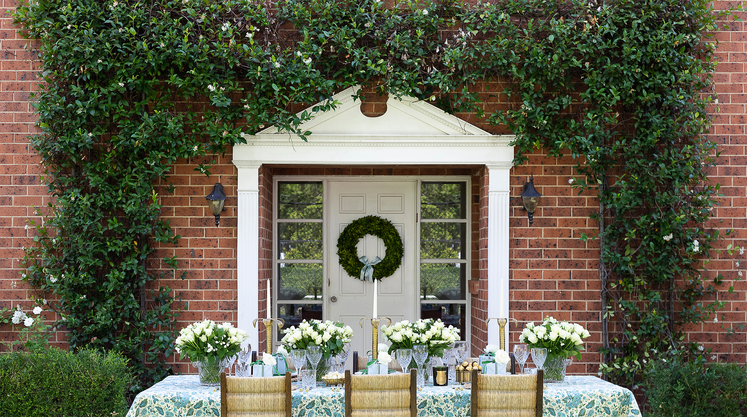 jasmine enveloping the facade and weathered wall sconces flanking the front door -