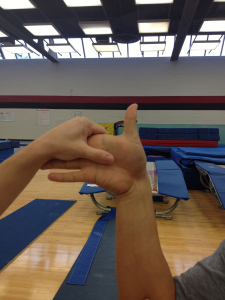 The hand is passively tilted toward the pinky until end range. A positive result is pain.