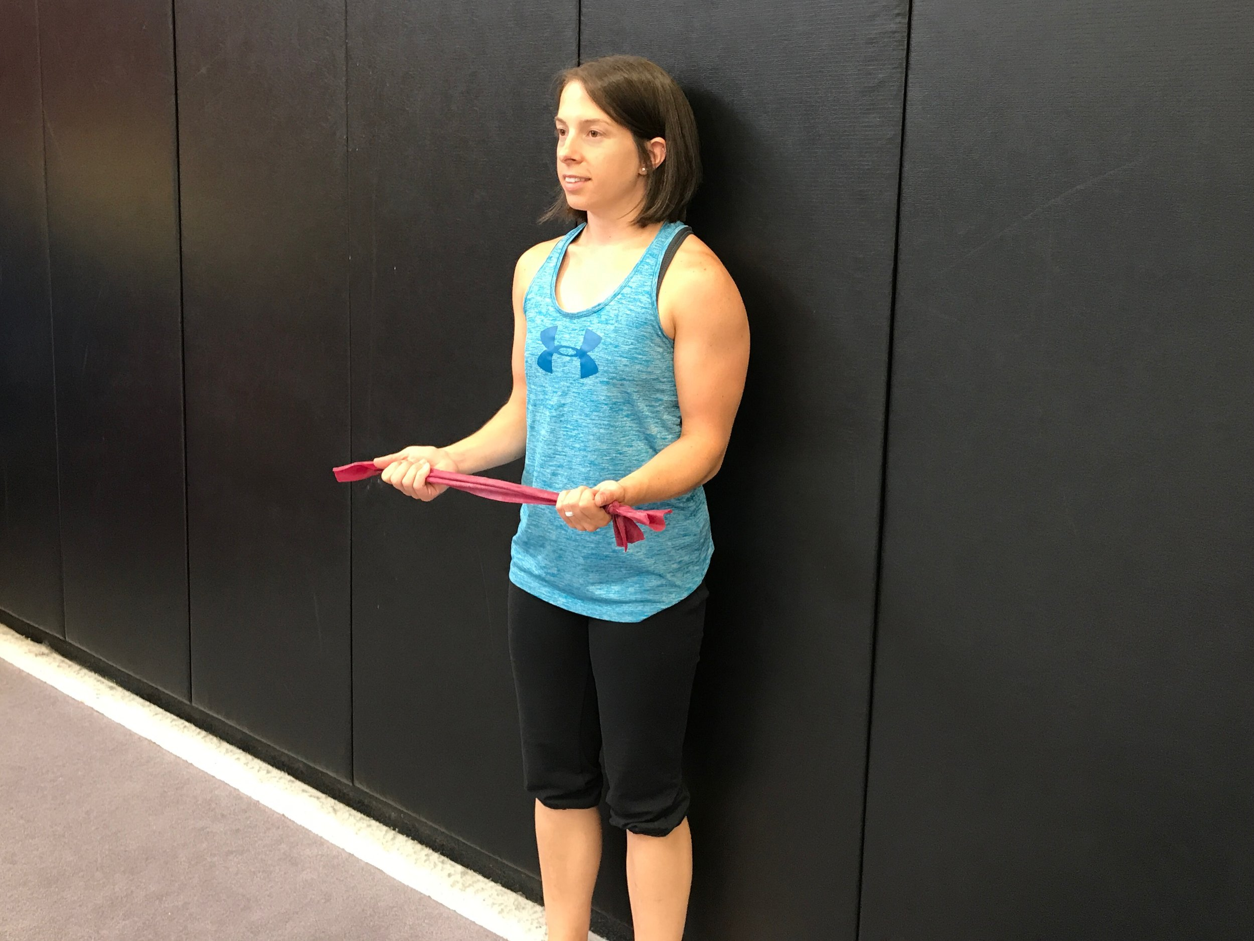 Starting position: Standing against the wall with your back flat, head neutral. Hold the band with palms up.  The elbows can be bent (as shown) or you can hold the arms more straight with the band down by the waist.