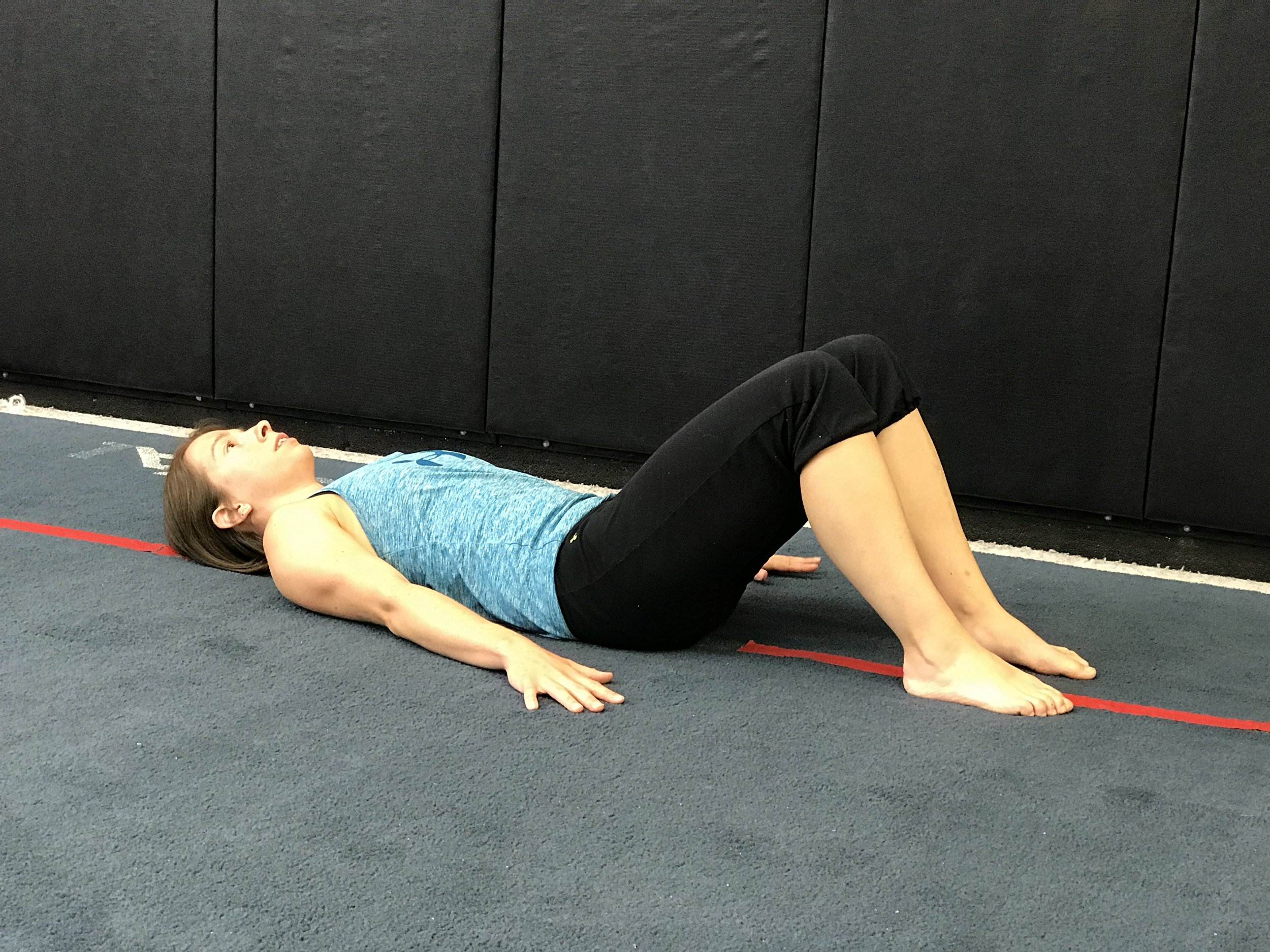 Starting position: Laying with the knees bent and feet flat.  Hands on the floor next to you for support/balance. Tighten the core (think abdominal brace/kegel).
