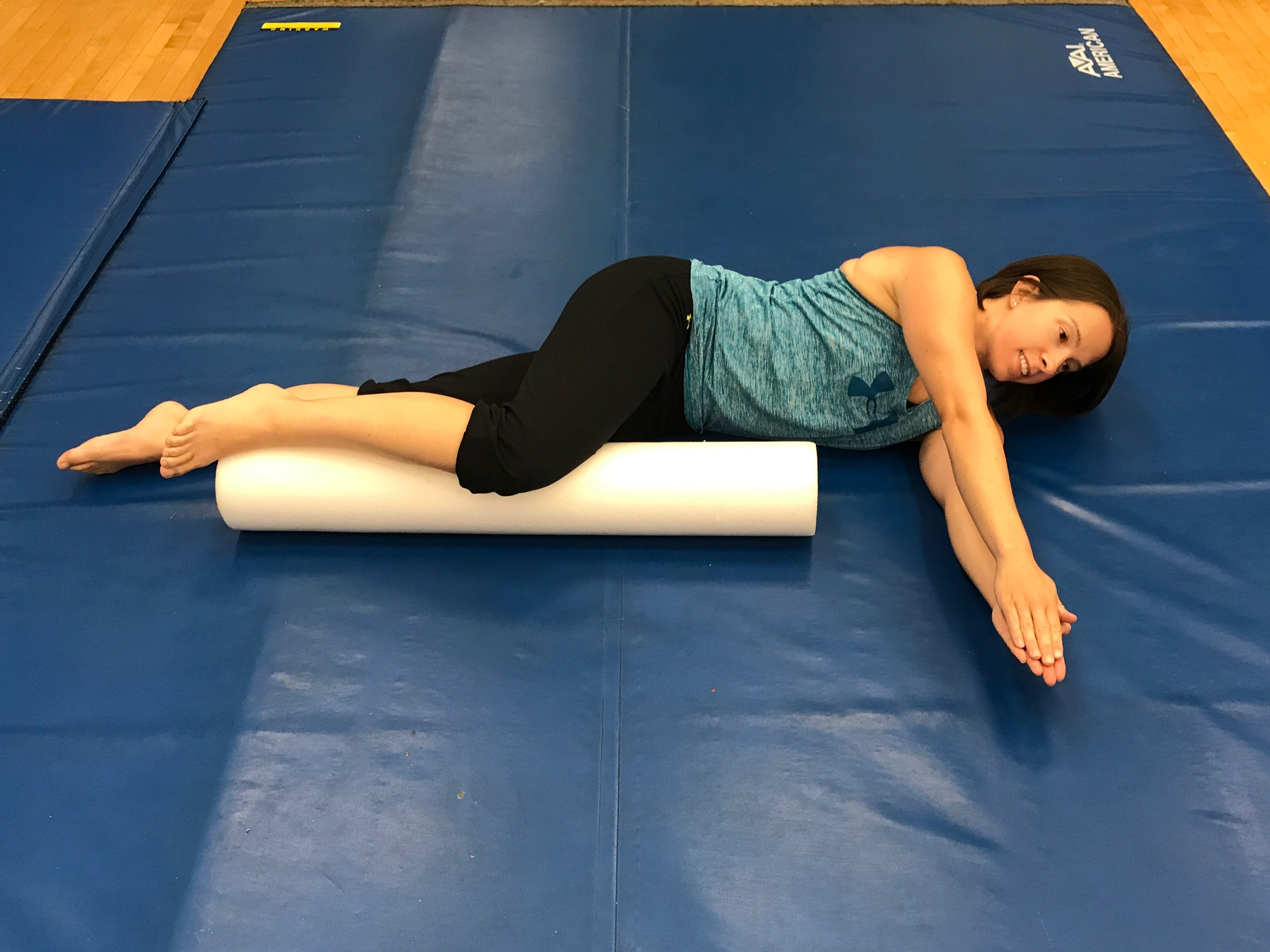 Starting position: Begin on your side with a foam roll under the top knee as shown. With the arms together, extend them out directly in front of you.