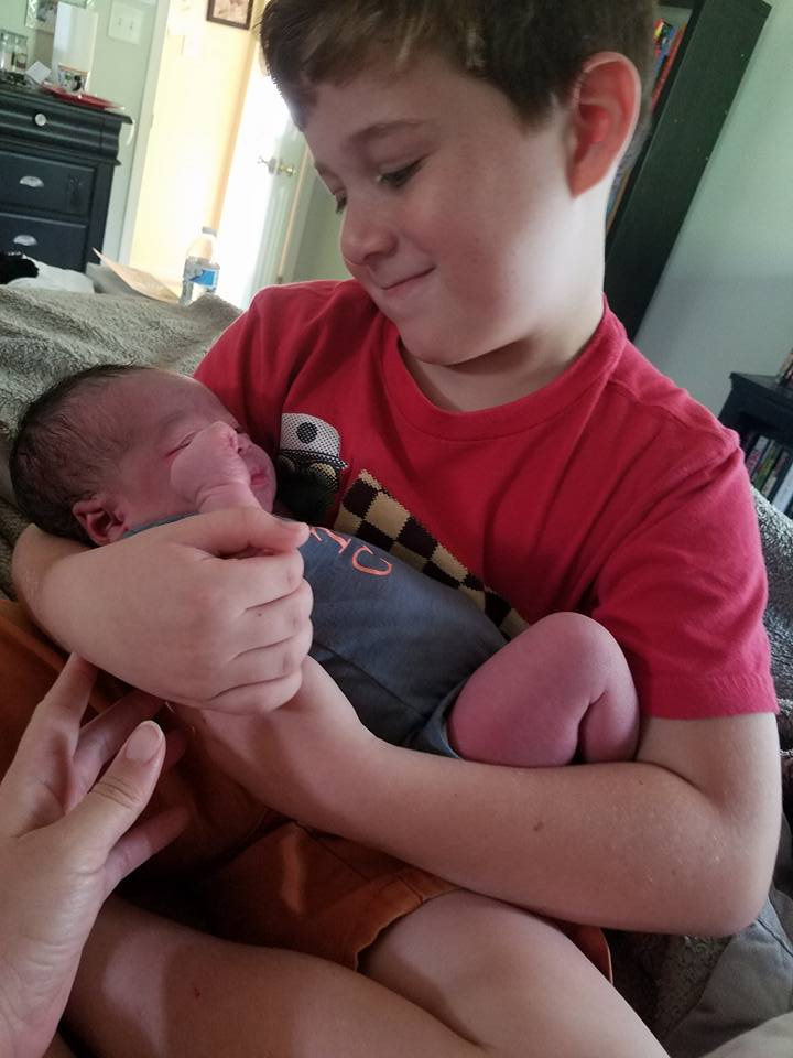 The author's middle child, Cayden, meeting his sister Thalia for the first time.
