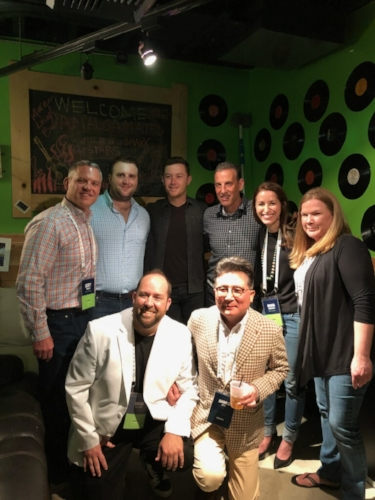 Top of the World leadership poses for a photo with country music singer Scotty McCreery at the 2018 IMGCL Seminar Party.