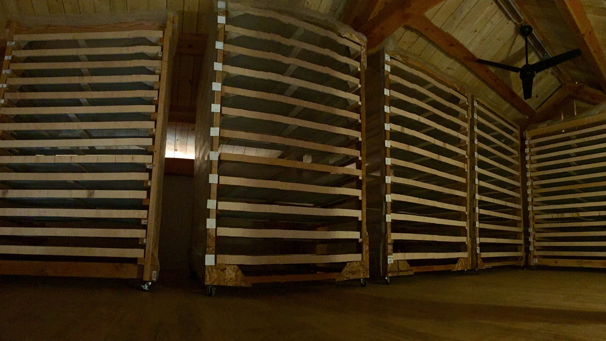 Step 7: Rack It - This is part 2 of our custom-designed herb drying process.Cleaned and bedded, the framed herbs are slid into these movable shelf units.In our drying loft, it is quiet and dark; the airflow is gentle and warm.It's the perfect conditions for drying the clean herbs.