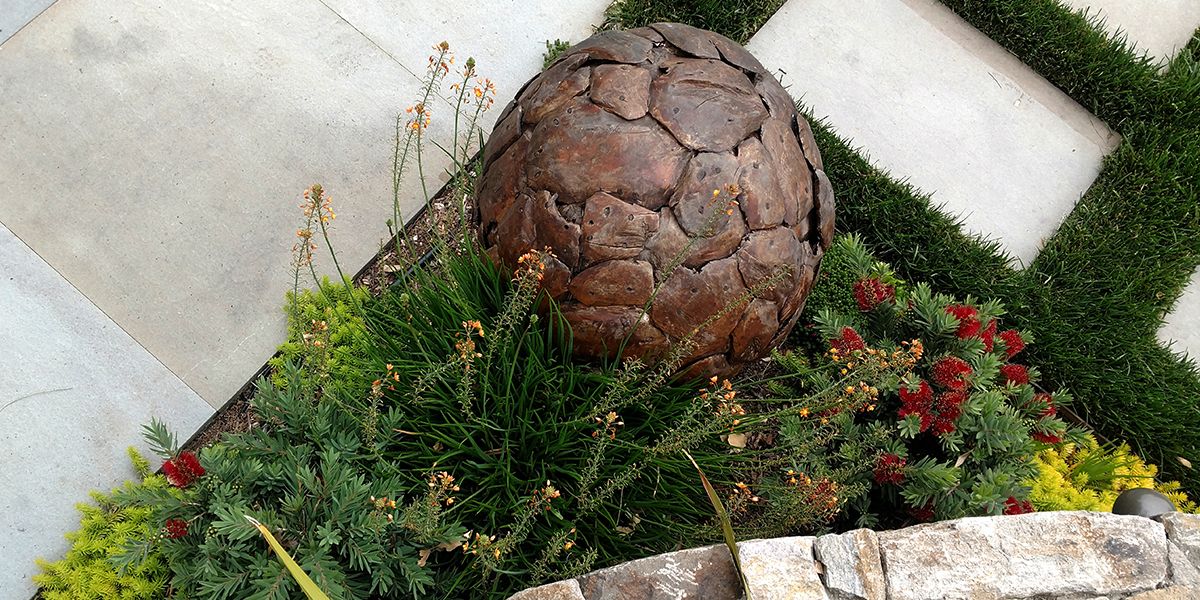 DETAILS  This one of a kind teak sculpture softens the space around this corner. The plantings bridge the grass steps to create continuity. Pops of color and texture finish the space and infuse accents to a naturally neutral palette.