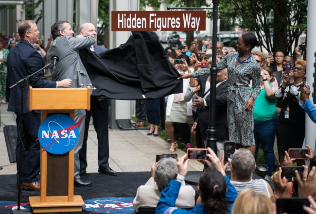 """The new street sign for Hidden Figures Way outside NASA headquarters in Washington is unveiled during a ceremony on June 12, 2019. (From left to right: NASA Administrator Jim Bridenstine, Sen. Ted Cruz, D.C. Council Chairman Phil Mendelson and """"Hidden Figures"""" author Margot Lee Shetterly.) - June 12, 2019  Image Courtesy: Joel Kowsky/NASA"""