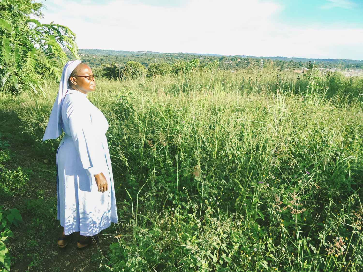 Sister Elizabeth Namazzi, of the Sisters of Mary, Mother of the Church, stands on the plot which will become the Ugandan Development Center for Early Mothers. As permits are secured and funds are raised, the land is being farmed.