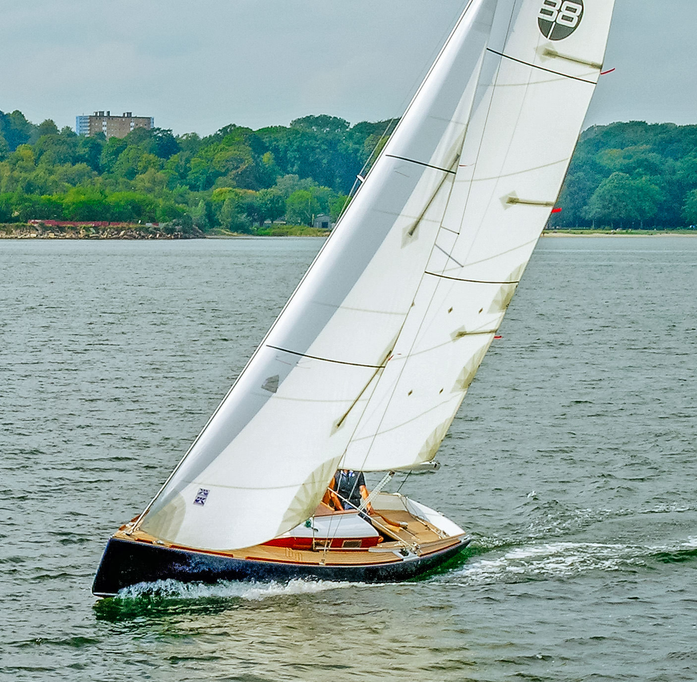 Modern classic daysailer with Dacron cruising mainsail and roller-furling jib with vertical battens.
