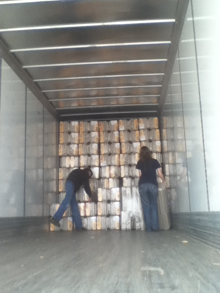 Cartons arrive in a semi and are unloaded by hand