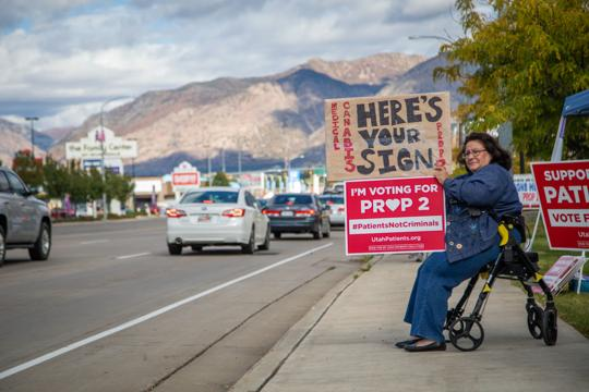Angela Urrea holds a Proposition 2 sign on Riverdale Road on Monday, Oct. 8, 2018. Proposition 2 is the initiative on the Nov. 6 ballot calling for the legalization of medical marijuana use.  BEN DORGER, Standard-Examiner