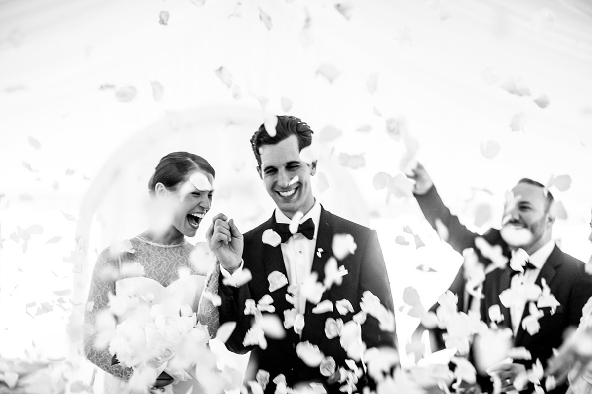 A black and white image of a bride and groom walking down the aisle after their wedding ceremony with flowers being thrown everywhere. by Vietnam based wedding photographer Justin Mott