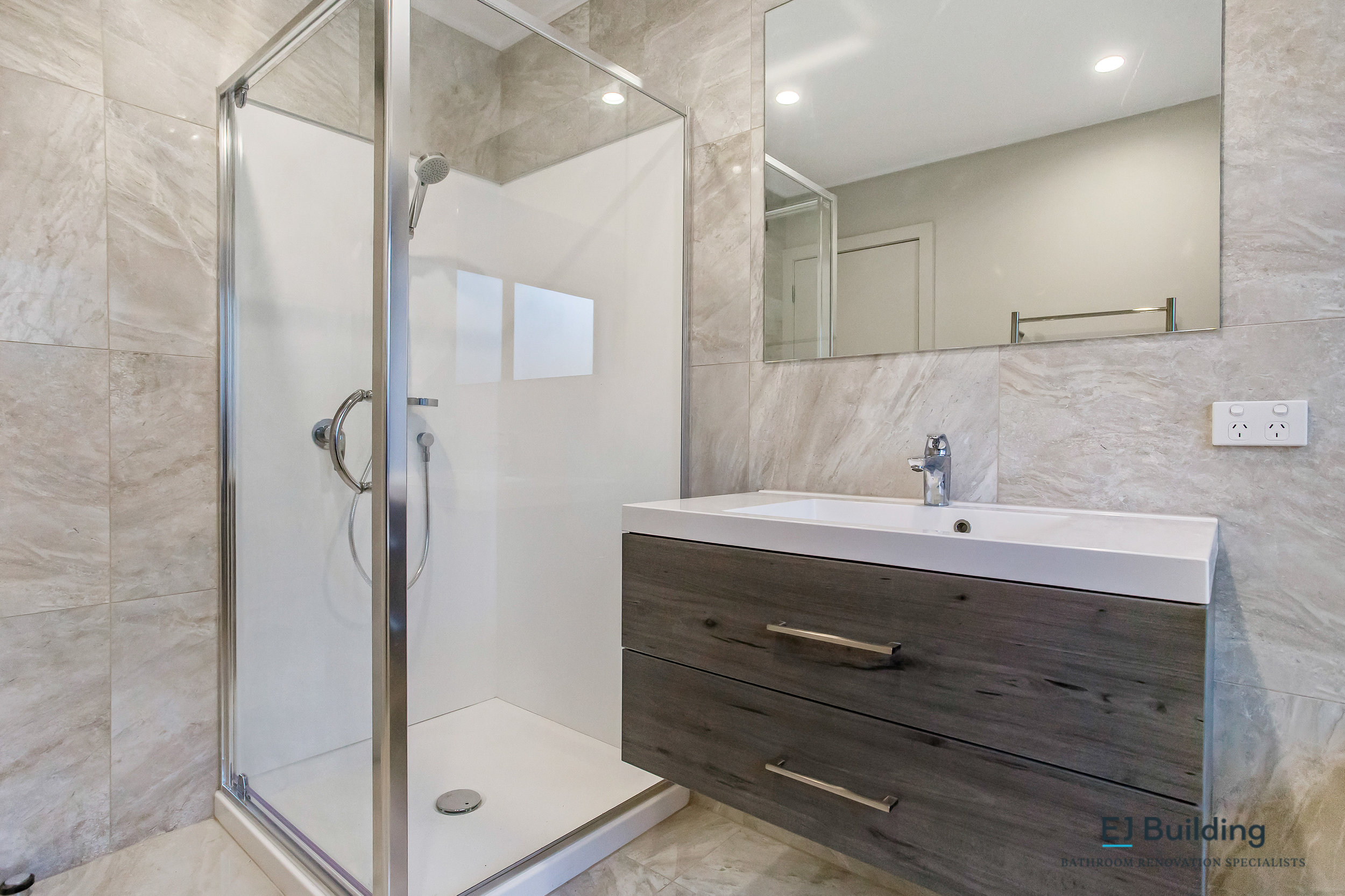 Acrylic shower in bathroom with tiled bathroom walls. In renovated bathroom in Auckland NZ.