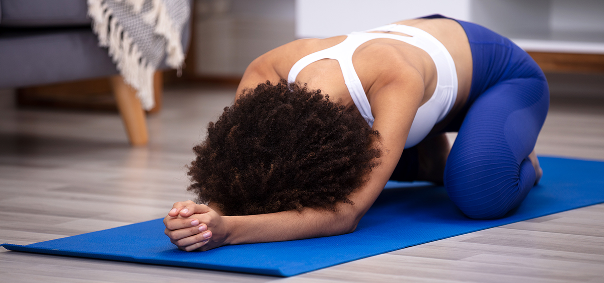 Athletic Woman Doing Yoga On Blue Fitness Mat Over The Hardwood