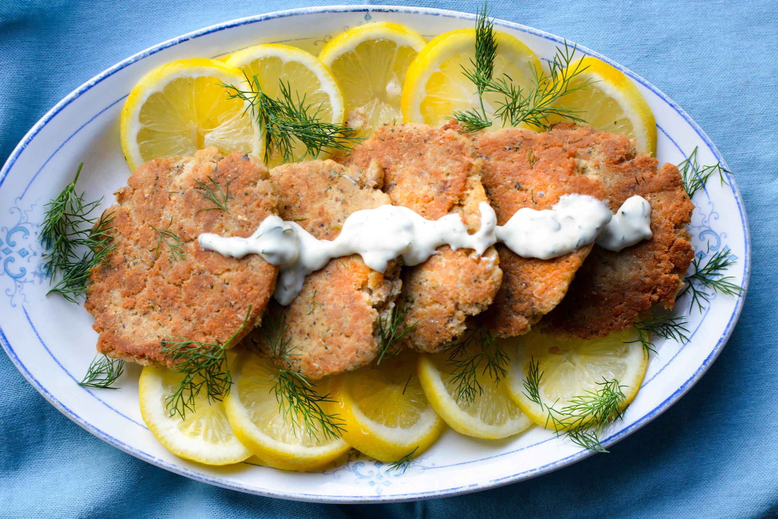 salmon cakes, sauce and lemons