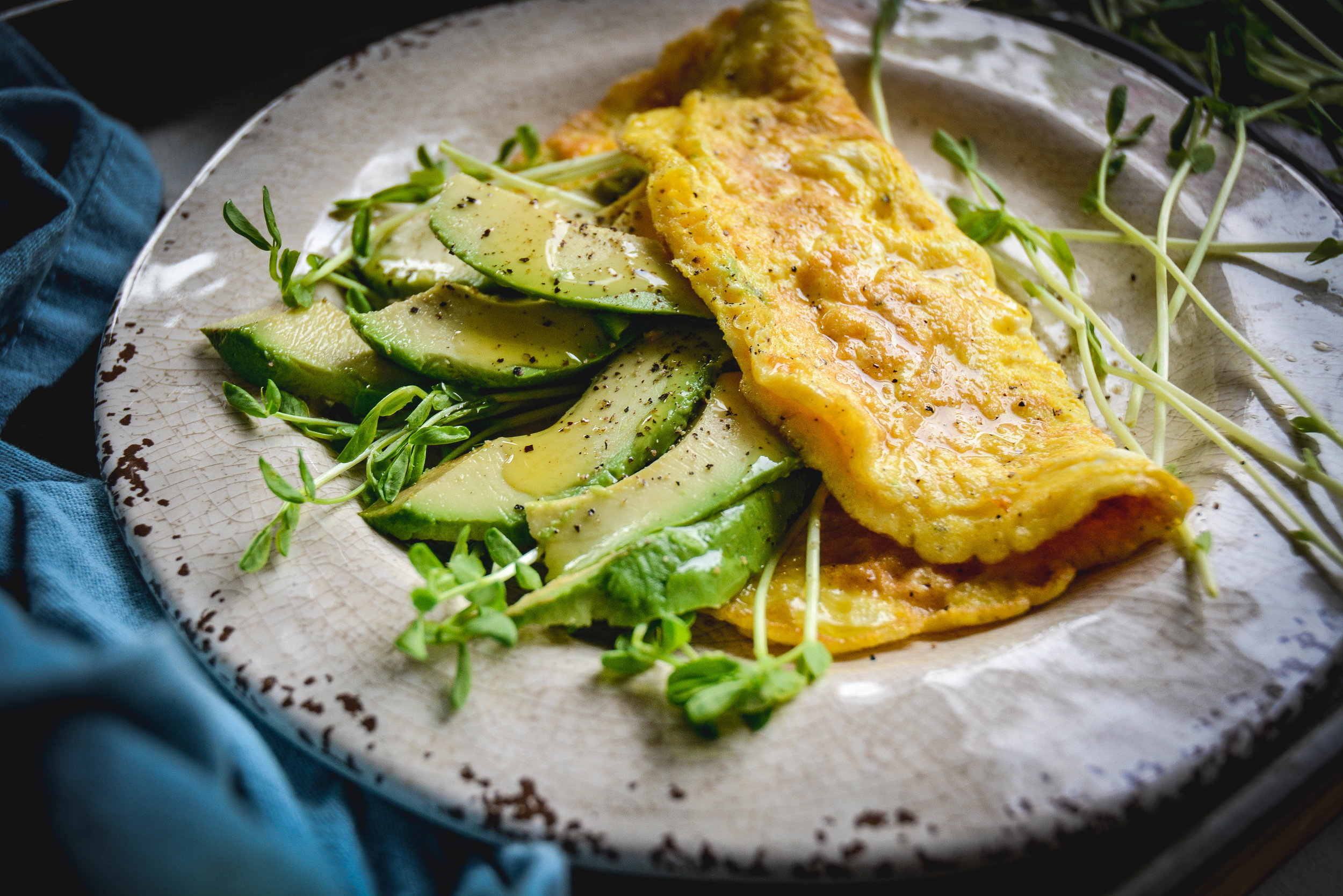 omelette with greens and avocado slices on plate