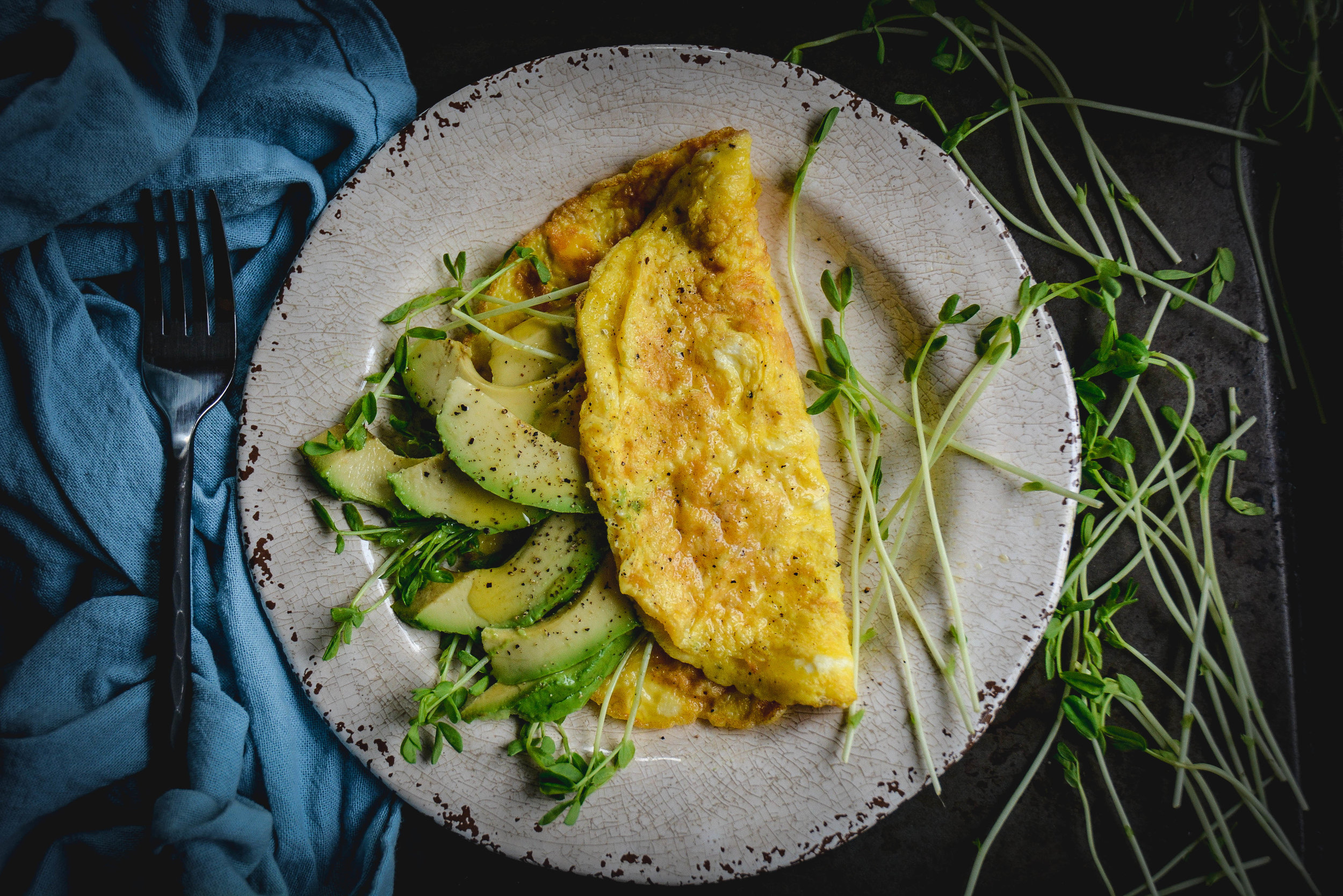 avocado slices in omelette on white plate, greens, napkin and fork
