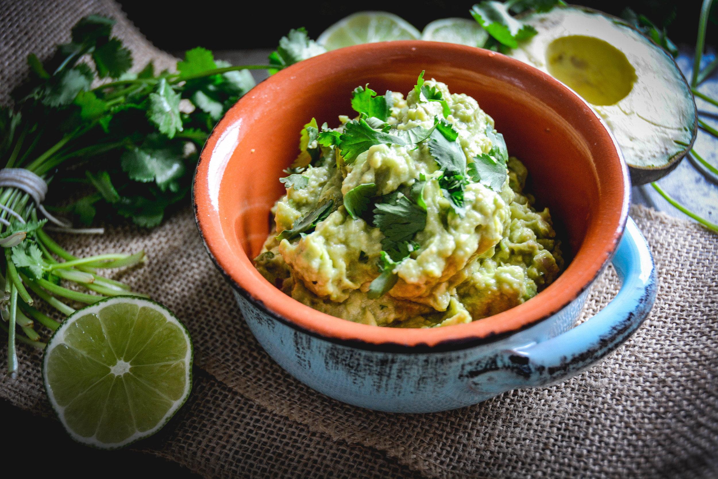 guacamole in bowl, lime and cilantro