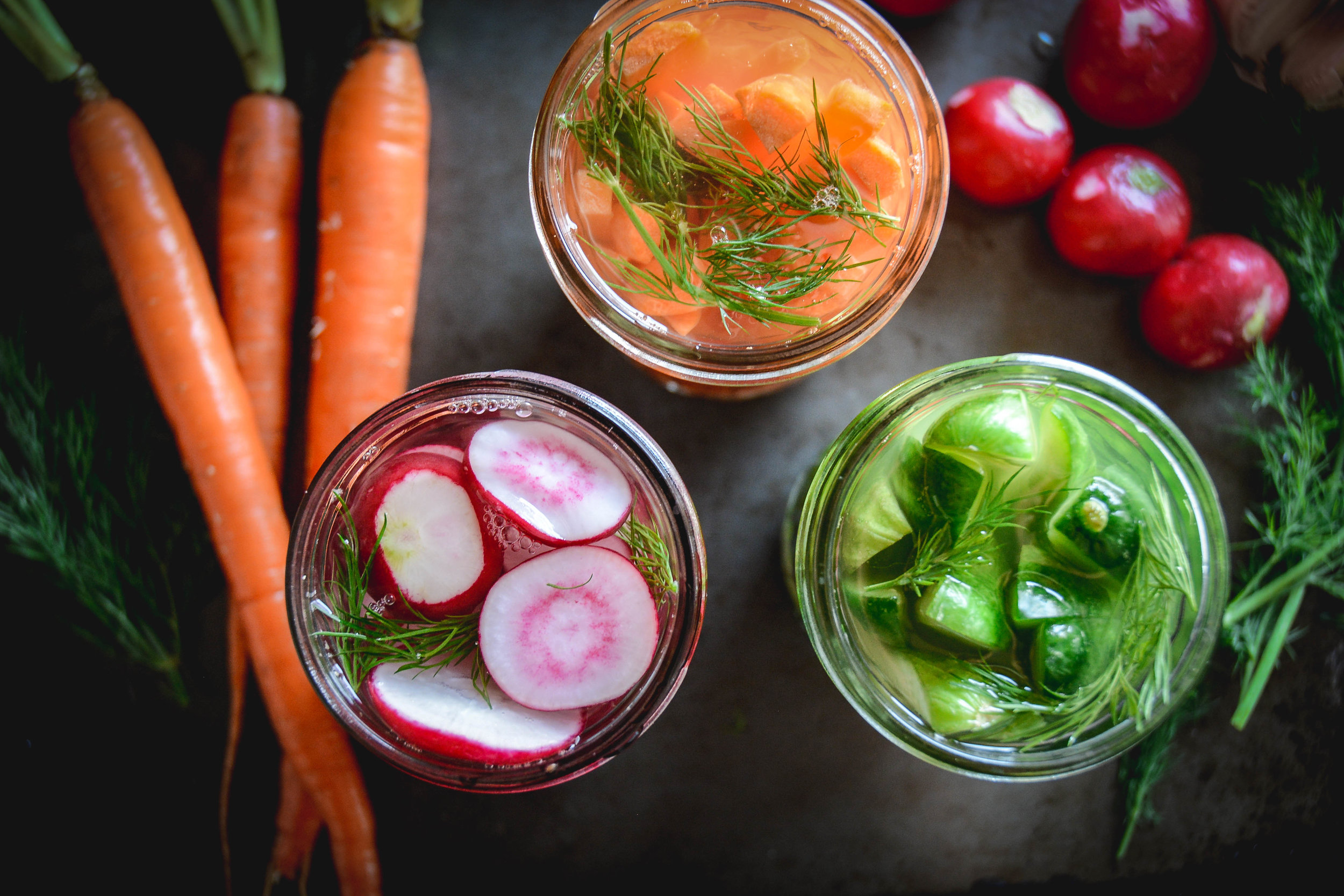carrots, pickles and radishes in jars with dill