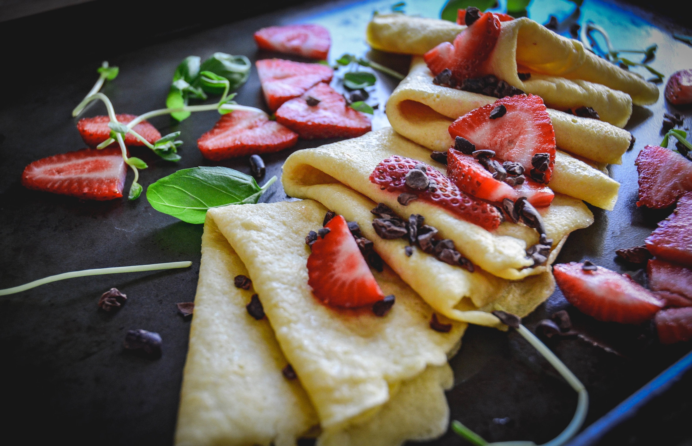 crepes and strawberres with cacao nibs