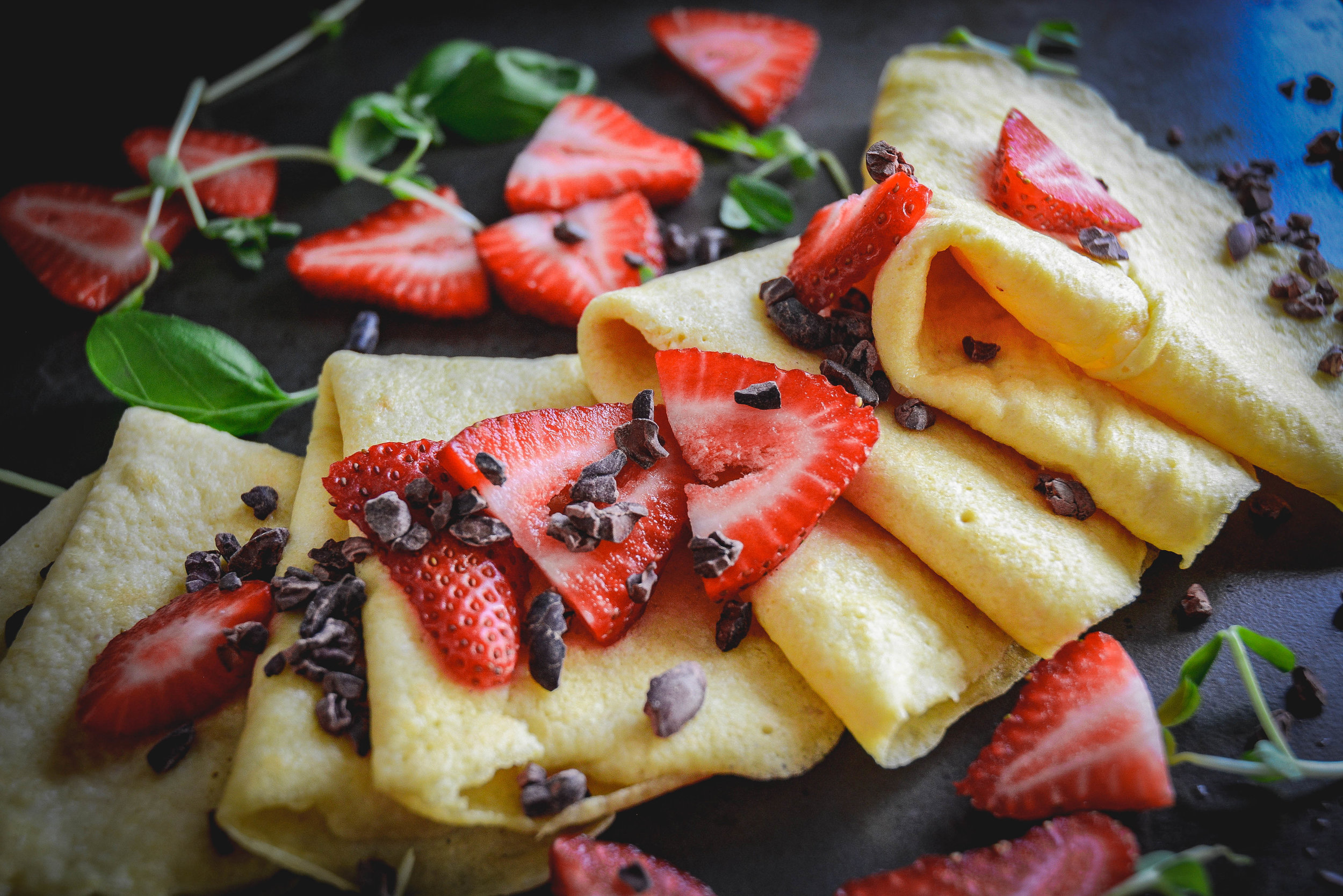 crepes strawberries, greens and cacao nibs