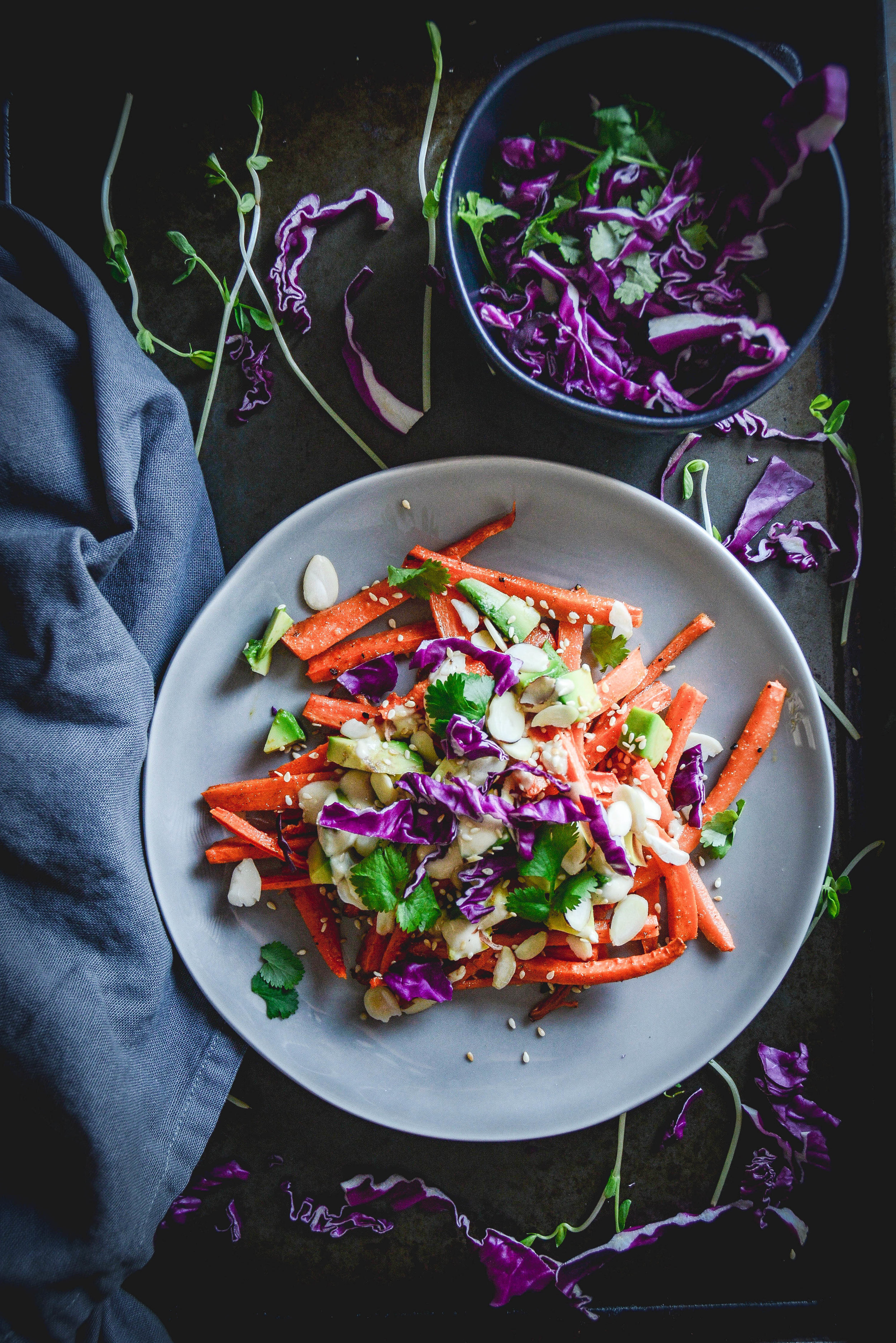 Cumin roasted carrots with avocado, tahini dressing and sesame seeds