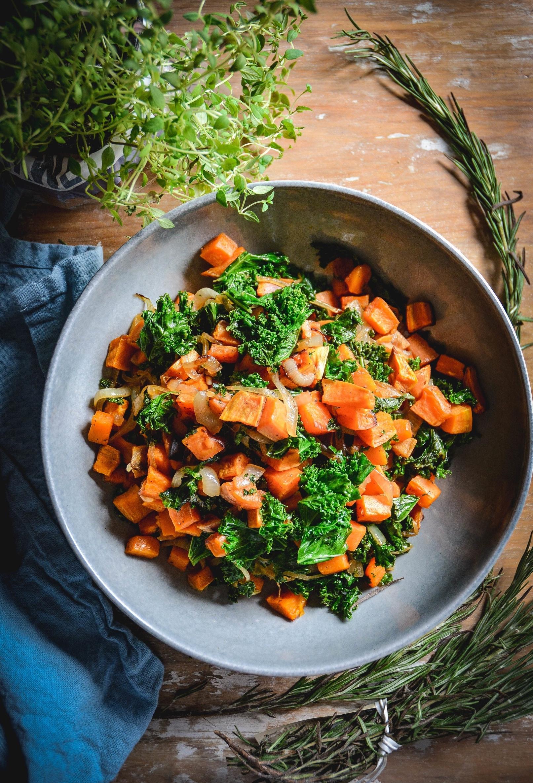 kale, sweet potatoes on plate, napkin and herbs